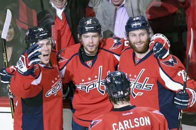 948bb39829d Washington Capitals center Evgeny Kuznetsov (92) is congratulated by Washington  Capitals right wing T.J. Oshie (L) and defenseman Karl Alzner (27) after ...