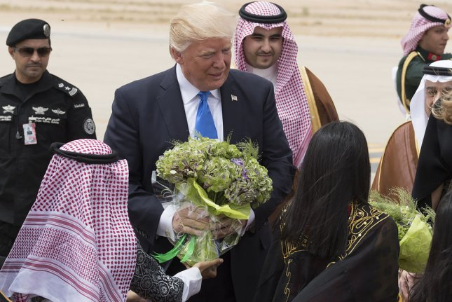 President Donald Trump and first lady Melania Trump are welcomed with bouquets of flowers on Saturday upon on their arrival in Saudi Arabia. White House Photo by Andrea Hanks/UPI