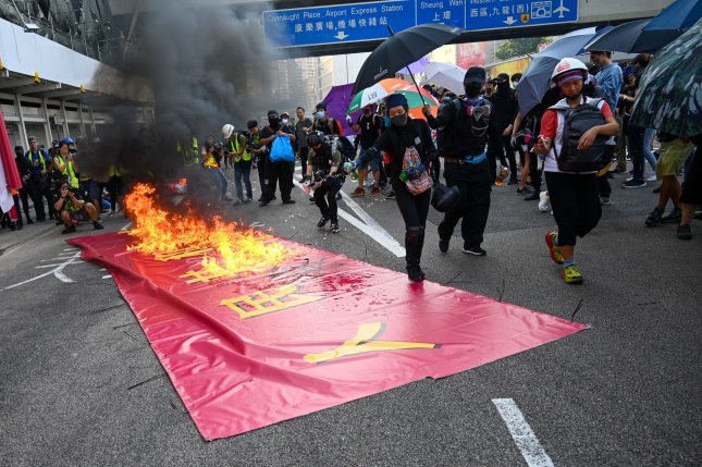 Protesters burn a sign celebrating the 70th anniversary of China during an anti-government rally in Hong Kong on October 1, 2019. Photo by Thomas Maresca/UPI