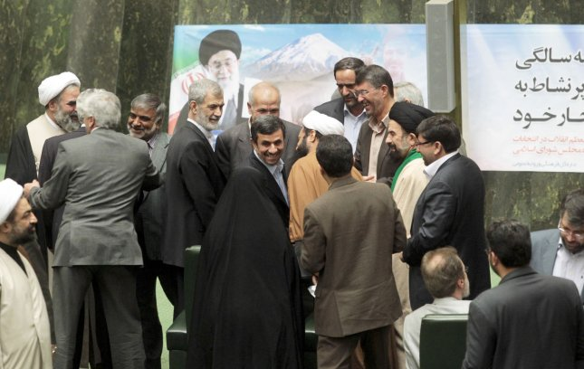 Iranian lawmakers surround President Mahmoud Ahmadinejad as he arrives to answer questions by members of parliament over his performance on political and economic issues Tehran, Iran on March 14, 2012. Ahmadinejad is the first president to face questions by parliament. UPI/Maryam Rahmanian.