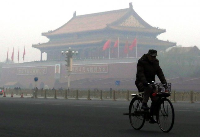 A bike-rider commutes under a thick smog near Tiananmen Square in Beijing on December 8, 2015. A restaurant in another smog-hit city, Zhangjiagang, was found to be charging customers an air cleaning fee. Photo by Stephen Shaver/UPI