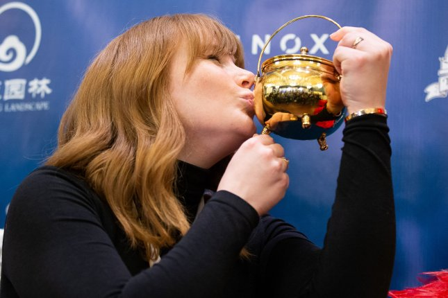 Actress Bryce Dallas Howard kisses her pudding pot trophy at a press conference after being honored as the Harvard University Hasty Pudding Theatricals 2019 Woman of the Year at Harvard University in Cambridge, Mass., on Thursday. Photo by Matthew Healey/UPI