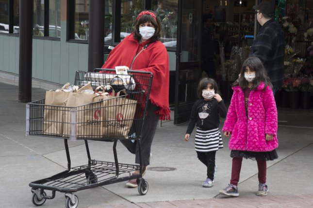 A new poll suggests the coronavirus has turned life upside down for many families in the United States. Pictured, a family leaves a grocery store after shopping in San Francisco in March. Photo by Terry Schmitt/UPI