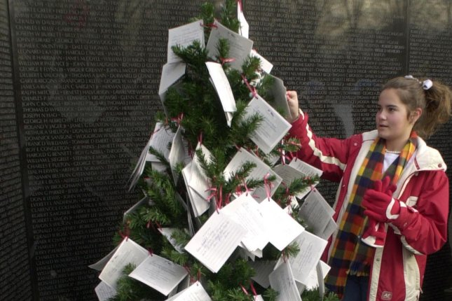 Annie Brindle of Chatsworth, Georgia, places a card on the Christmas tree at the Vietnam Veterans Memorial in Washington, D.C. Photo by Bill Clark/UPI