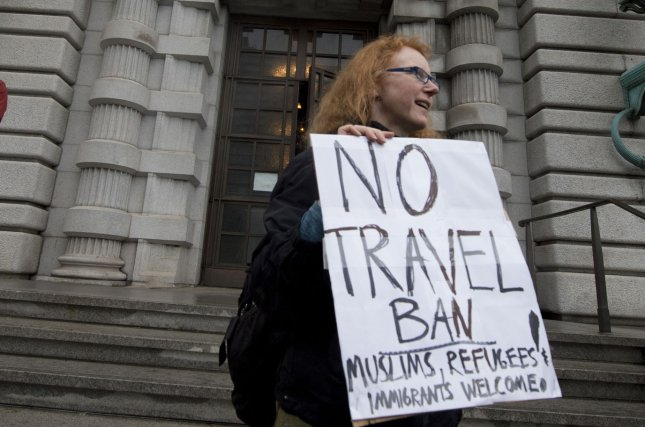A protester holds a sign in front of the 9th U.S. Circuit Court of Appeals in San Francisco on February 7, demonstrating against the president's so-called travel ban to keep refugees and migrants out of the United States. File Photo by Terry Schmitt/UPI