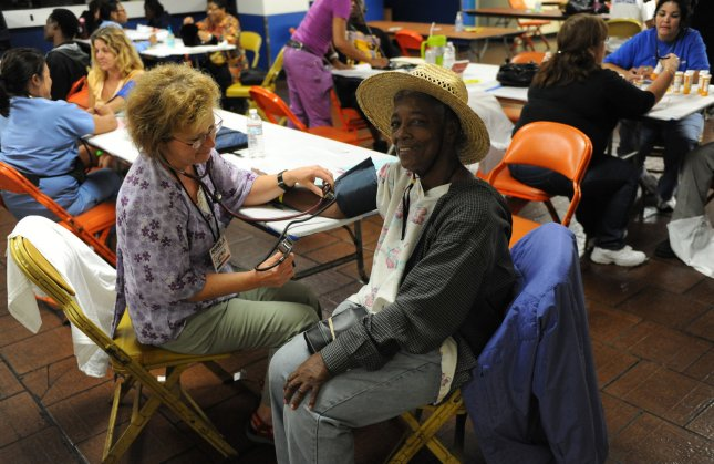 Patients have their blood pressure taken, at a large health care clinic set up by Remote Area Medical at the Forum in Inglewood, California on August 15, 2009. The Los Angeles event marks the first time Remote Area Medical has provided such medical care in a major urban area. The group typically serves patients in remote, rural parts of the United States and travels to underdeveloped countries. UPI/Jim Ruymen.