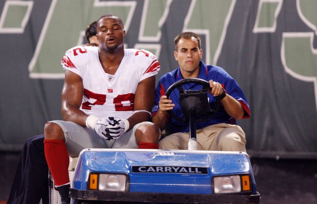 New York Giants defensive end Osi Umenyiora gets carted off of the field after injuring his left knee against the New York Jets Aug. 23, 2008. (UPI Photo/John Angelillo) .