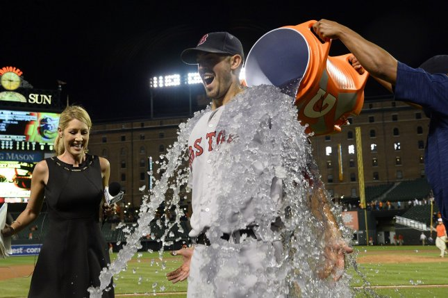 Boston Red Sox starting pitcher Rick Porcello is dunked with ice water after throwing a 5-2 win complete game on 89 pitches with 65 strikes against the Baltimore Orioles while television reporter Guerin Austin looks on at Camden Yards in Baltimore, September 19, 2016. Photo by David Tulis/UPI