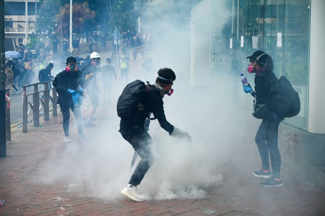 A protester is surrounded by a cloud of tear gas during an anti-government rally in Hong Kong on Sunday. Photo by Thomas Maresca/UPI