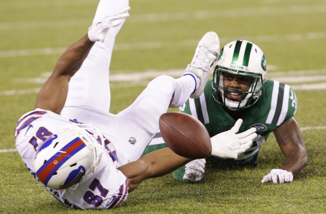 The New York Jets' Juston Burris watches as Buffalo Bills receiver Jordan Matthews fumbles during the first half of their game Thursday. Photo by John Angelillo/UPI