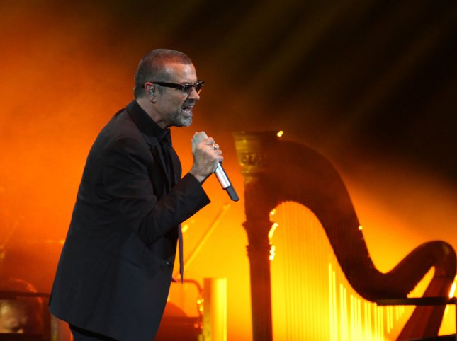 George Michael, accompanied by a symphony orchestra, performs in concert at Bercy in Paris on October 3, 2011. Michael was buried during a private funeral ceremony on Wednesday, three months after he died on Christmas Day at the age of 53. File Photo by David Silpa/UPI