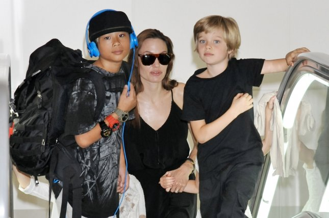Angelina Jolie (C) and children Shiloh (L) and Pax arrive at Tokyo International Airport in Tokyo, Japan, on June 21, 2014. Jolie and Brad Pitt have reached an agreement where the actress will retain custody of their six children. File Photo by Keizo Mori/UPI