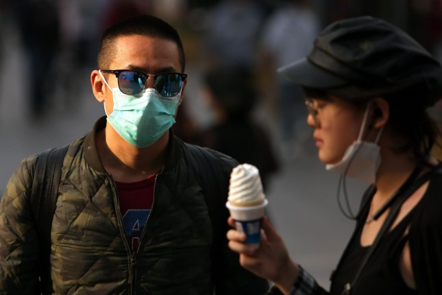 People wear protective face masks while walking through a shopping area Tuesday in Beijing. Photo by Stephen Shaver/UPI