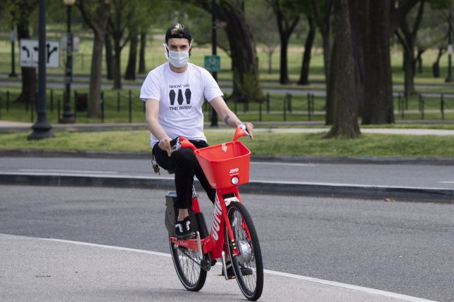 A man rides a bike on a warm day during the coronavirus pandemic in Washington, D.C., on Wednesday. Photo by Kevin Dietsch/UPI