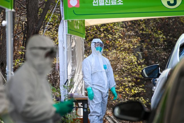 Health workers in protective suits test potential coronavirus patients at a drive-through center at Seoul Metropolitan Eunpyeong Hospital on March 4. File Photo by Thomas Maresca/UPI