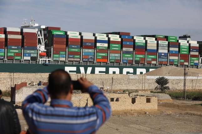 Bystanders watch as the Ever Given container ship is dislodged from the banks of the Suez Canal in Egypt on March 29. Photo by Karem Ahmed/ UPI