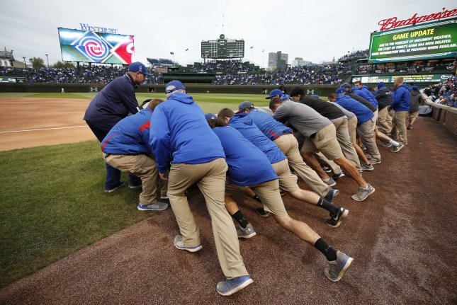 Chicago Cubs ground crew members cover the field during a weather delay in game 4 of the NLDS at Wrigley Field on October 10, 2017, in Chicago. Photo by Kamil Krzaczynski/UPI