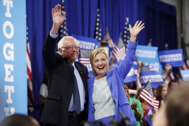 Bernie Sanders and Hillary Clinton wave to the crowd after Sanders gave Clinton his formal endorsement during a rally at Portsmouth High School in New Hampshire earlier this month. Emails hacked from the Democratic National Committee show staff members biased toward Clinton despite the DNC being officially neutral during the primaries. Photo by Matthew Healey/UPI