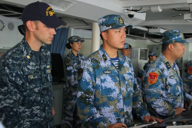 Service members from Chinese and U.S. navies observe a gun exercise from the bridge of Chinese Navy multirole frigate Hengshui (572), during the Rim of the Pacific exercises in July. A Chinese naval commander who was the first to participate in U.S.-led Pacific Rim Navy drills has been promoted to head Beijing's naval forces. File Photo by PLA Navy/UPI