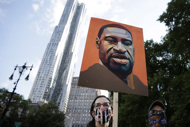 A protester holds a painting of George Floyd as activists gather near New York City Hall on June 25. Floyd's death in police custody spawned demonstrations worldwide calling for police reforms and new criminal justice legislation. Photo by John Angelillo/UPI