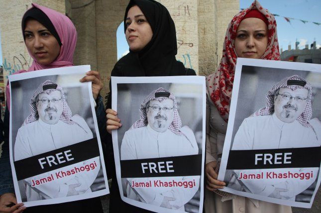 Palestinian activists hold posters of Saudi journalist Jamal Khashoggi in Rafah, Gaza Strip, in October. Photo by Ismael Mohamad/UPI