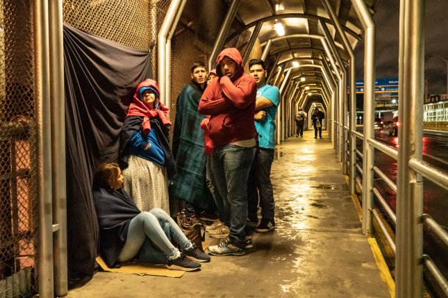 A group asylum seekers from Venezuela sit in the cold and wait to cross the U.S. border from Reynosa, Mexico, on January 26. In an agreement between the United States and Mexico reached Friday, asylum seekers will be returned to Mexico to await adjudication of their claims, and authorize their entrance for humanitarian reasons. File photo by Ken Cedeno/UPI
