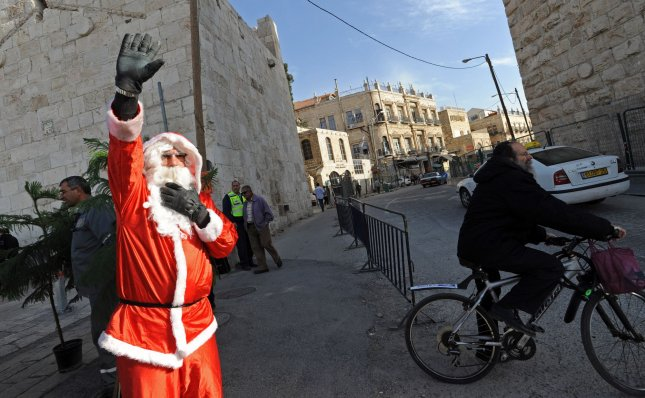 Palestinian Christian Issa Kassissieh, dressed as Santa Claus, waves to tourists during the distribution of Christian trees to Christian residents of Jerusalem outside the Jaffa Gate in the Old City of Jerusalem, December 22, 2010. UPI/Debbie Hill