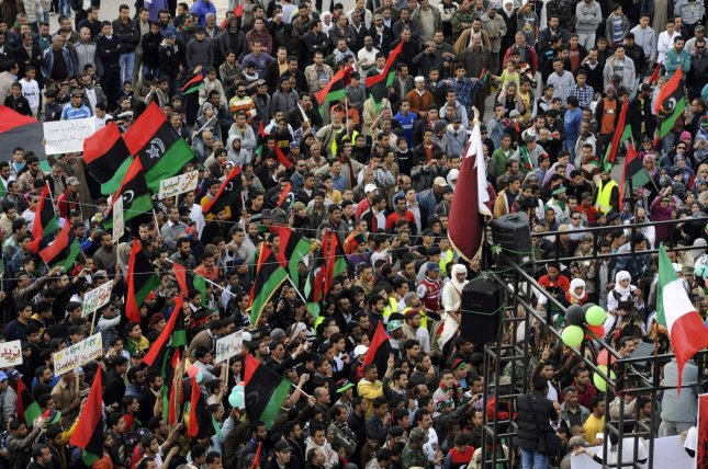Witnesses said at least 10 blasts were heard as NATO's air campaign continued in Tripoli, bombing locations near Gadhafi's compound. Below, Libyans protesters hold old Libyan flags during a protest in Benghazi in eastern Libya, on April 21 2011. UPI\Tarek Alhuony.