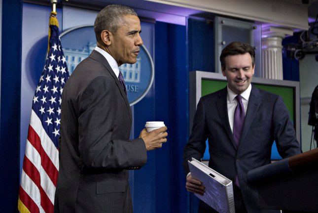 President Barack Obama makes a surprise visit to journalism students participating in a college reporter day next to Press Secretary Josh Earnest on April 28. The editor of the Rutgers University student paper asked Obama for an exclusive interview. Pool Photo by Andrew Harrer/UPI