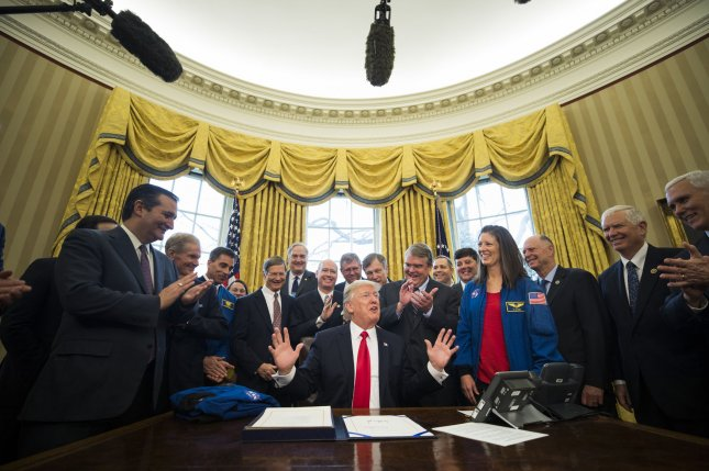 U.S. President Donald Trump prepares to sign the NASA Transition Authorization Act in the Oval Office of the White House in Washington, D.C., on Tuesday, which boosts NASA's budget -- much of which will be directed toward pursuit of a mission to Mars. Pool Photo by Jim Lo Scalzo/UPI
