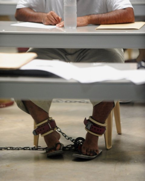 Detainees attend a class at Camp VI in Camp Delta at Naval Station Guantanamo Bay in Cuba on July 8, 2010. Detainees are shackled to the floor when contractors are teaching classes to insure teachers' safety. UPI/Roger L. Wollenberg