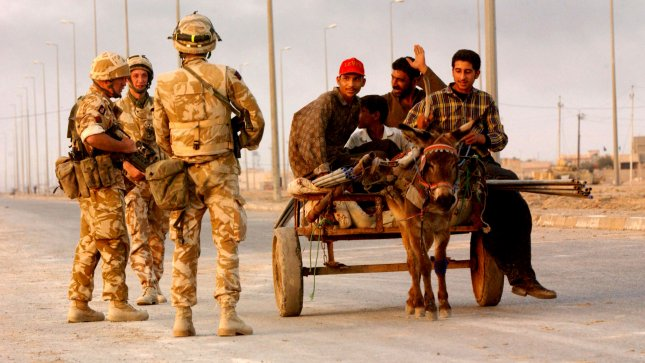 A burrow pulls a wagon of Iraqis past a checkpoint of British troops, just outside of the city of Basra. UPI File/Chris Corder