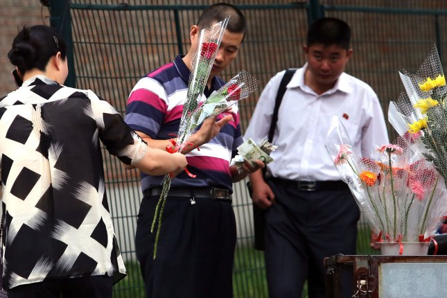 North Koreans buy flowers from Chinese vendors just outside their embassy gate in Beijing. North Koreans said nuclear weapons should never be abandoned and spoke unfavorably about the United States, according to a Chinese journalist. File Photo by Stephen Shaver/UPI