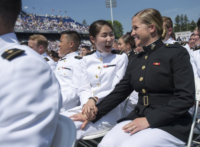 Graduating Midshipman Judith Cho (L) congratulates classmate Michaela Connally after she took the oath of office during the 2016 graduation and commissioning ceremony at the U.S. Naval Academy in Annapolis, Md., on May 27, 2016. On December 3, 2015, Defense Secretary Ashton Carter announced all combat roles in the U.S. armed forces would be opened to women. File Photo by Kevin Dietsch/UPI