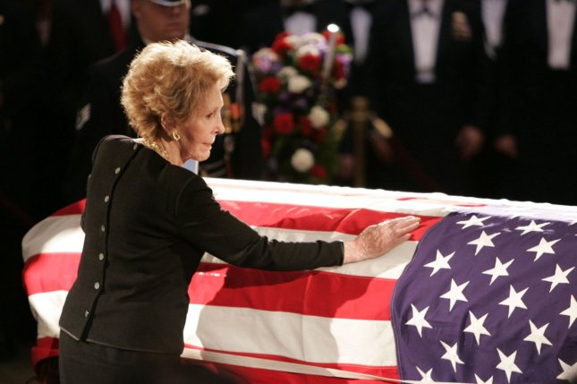 Former first lady Nancy Reagan touches the casket of her husband, former President Ronald Reagan, in the Capitol Rotunda on June 9, 2004. He died June 5 at age 93. File Photo by Peter Jones/UPI