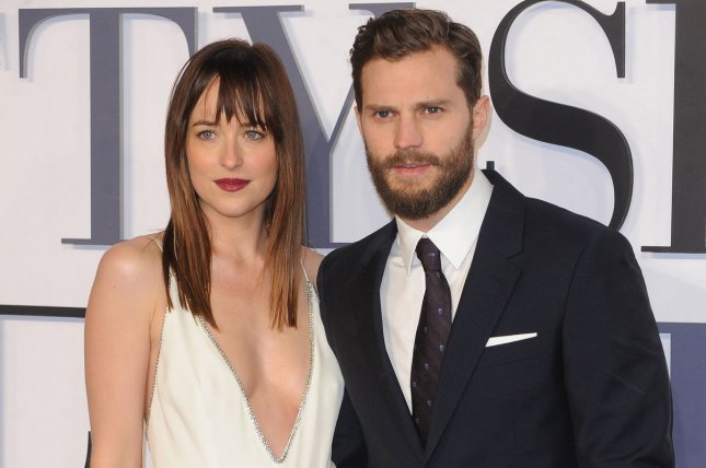 Jamie Dornan (R) and Dakota Johnson at the London premiere of Fifty Shades of Grey on February 12, 2015. The co-stars were spotted kissing on the Fifty Shades Darker set Tuesday. File Photo by Paul Treadway/UPI