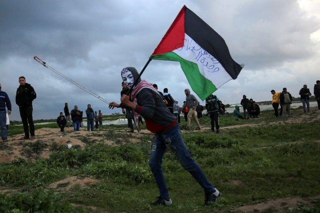 A Palestinian demonstrator wears a mask as he slings stones at Israeli forces during a protest at the Israel-Gaza border fence east of Gaza City on March 1. Photo by Ismael Mohamad/UPI