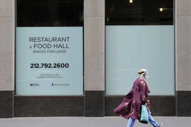 A woman wears a protective face mask and shield while walking by a space for lease sign in Rockefeller Center in New York City in June. Photo by John Angelillo/UPI