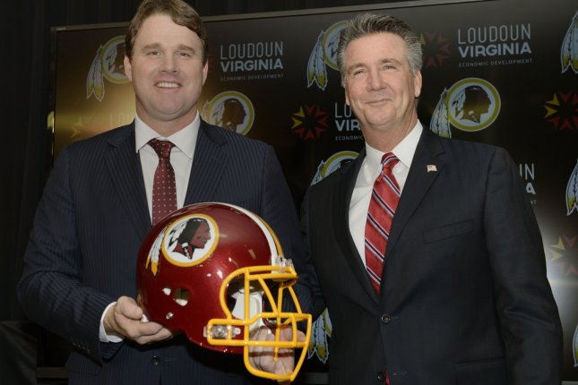 The Washington Redskins new head coach Jay Gruden (L) holds a helmet as he poses with General Manager and Team President Bruce Allen after a press conference. UPI/Mike Theiler