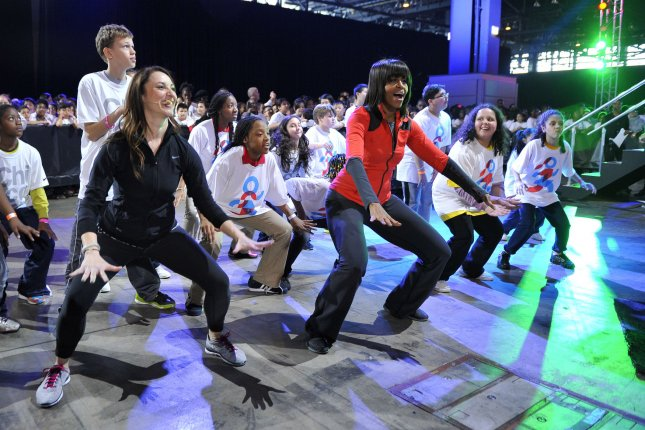 """Study finds most states' physical education standards lacking. Pictured, first lady Michelle Obama dances with Chicago students at her """"Bringing Physical Activity Back to Schools"""" event at McCormick Place in Chicago on the third anniversary of her Let's Move anti-obesity program in 2013. File photo by Brian Kersey/UPI"""
