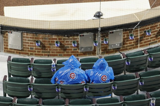 Fans wait during a rain delay for the opening day game between the Chicago Cubs and Los Angeles Dodgers on April 10 at Wrigley Field in Chicago. File Photo by Kamil Krzaczynski .