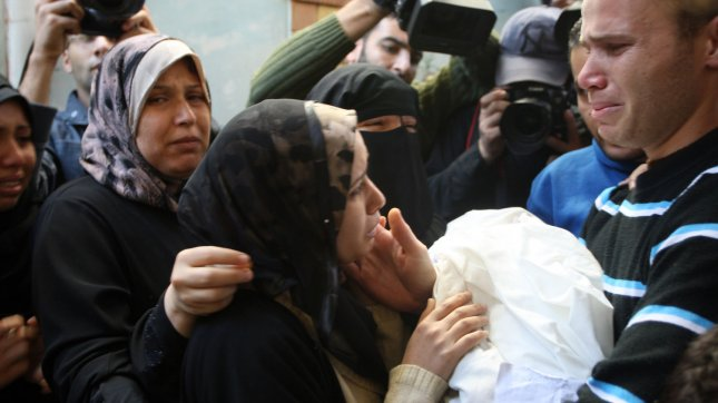 The parents of 11 month-old Palestinian baby Ahmed Masharawi, killed in an Israeli strike, hold his body during his funeral in Gaza City, Thursday, November. 15, 2012. The violence sparked a furious response from Egypt's Islamist administration, which has close ties with Gaza's ruling Hamas movement, with Cairo recalling its ambassador in protest at Israel's killing of Hamas military chief Ahmed Jaabari. UPI/Ismael Mohamad