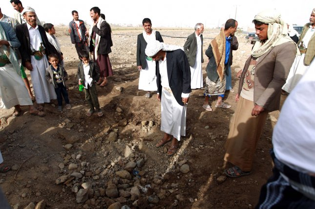 Yemenis gather around a crater left following a reported airstrike on March 28, 2015, in the capital Sanaa on the third day of Saudi-led coalition airstrikes against Houthis. On May 3, 2015, Human Rights Watch accused the Saudi-led coalition of using U.S.-manufactured cluster bombs that have been banned by a large portion of the international community. Photo by Mohammad Abdullah/UPI