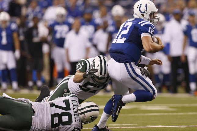 Indianapolis Colts quarterback Andrew Luck (12) fights to break free from New York Jets' Trevor Reily (57) and Leger Douzable (78). Photo by John Sommers II/UPI