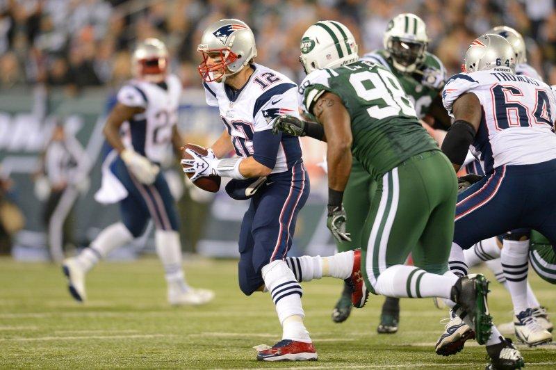New England Patriots quarterback Tom Brady (12) scrambles from former New York Jets defensive end Quinton Coples (98). UPI/Rich Kane