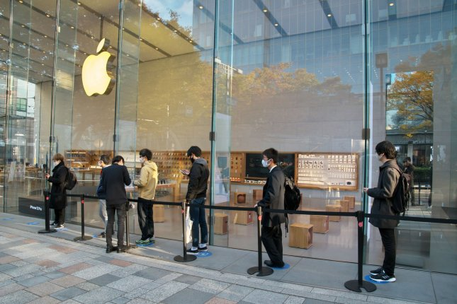 Customers wait in a line to buy the new iPhone 12 during the launch day at Apple Omotesando store in Tokyo on Friday. Photo by Keizo Mori/UPI