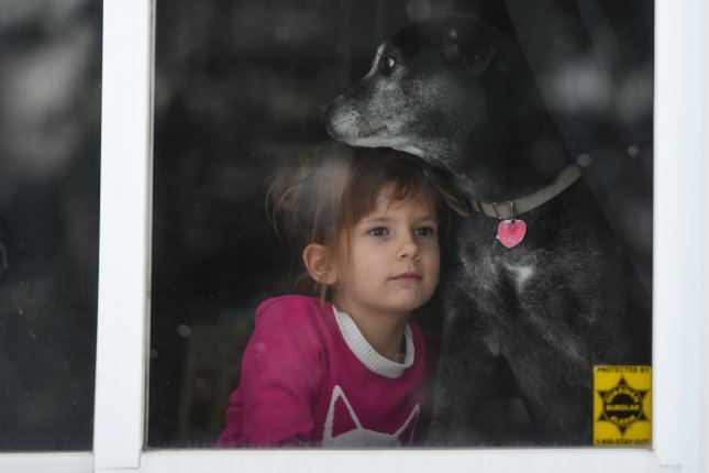 Six-year-old Lucy Norman watches with her dog Rory as volunteers deliver cases of bottled water in her neighborhood in Flint, Michigan, on March 5, 2016. File Photo by Molly Riley/UPI
