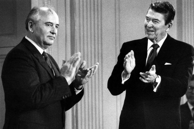 President Ronald Reagan (R) and Soviet leader Mikhail Gorbachev applaud after signing the historic arms control agreement banning intermediate-range nuclear missiles in the East Room of the White House on December 8, 1987. UPI File Photo