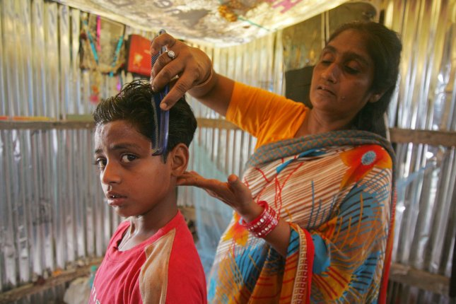 Shamim Begum, mother of Indian Muslim and Slumdog Millionaire child actor Mohammed Azharuddin Ismail combs his child hair inside a slum in East Bandra in Mumbai, India on March 16, 2009. (UPI Photo/Mohammad Kheirkhah)