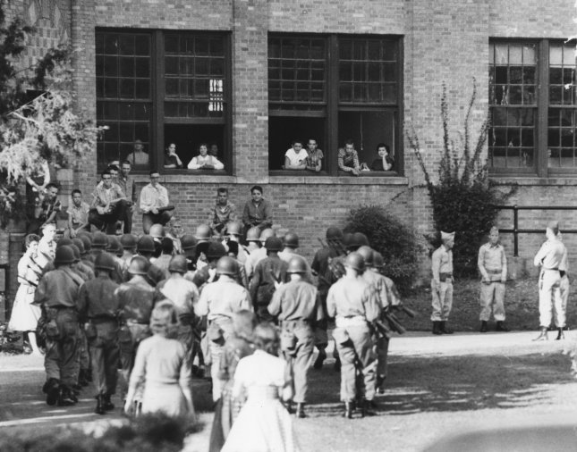 Original caption: A platoon of National Guardsmen escorts nine Negro students into Little Rock Central High School to attend classes on October 10, 1957. President Eisenhower was compelled to enforce the Supreme Court's public school desegregation decision with troops after the integrity of the court was challenged by Arkansas Governor Orval Faubus. (UPI Photo/Files).